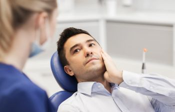 man holding his mouth in pain while sitting on a dentist chair